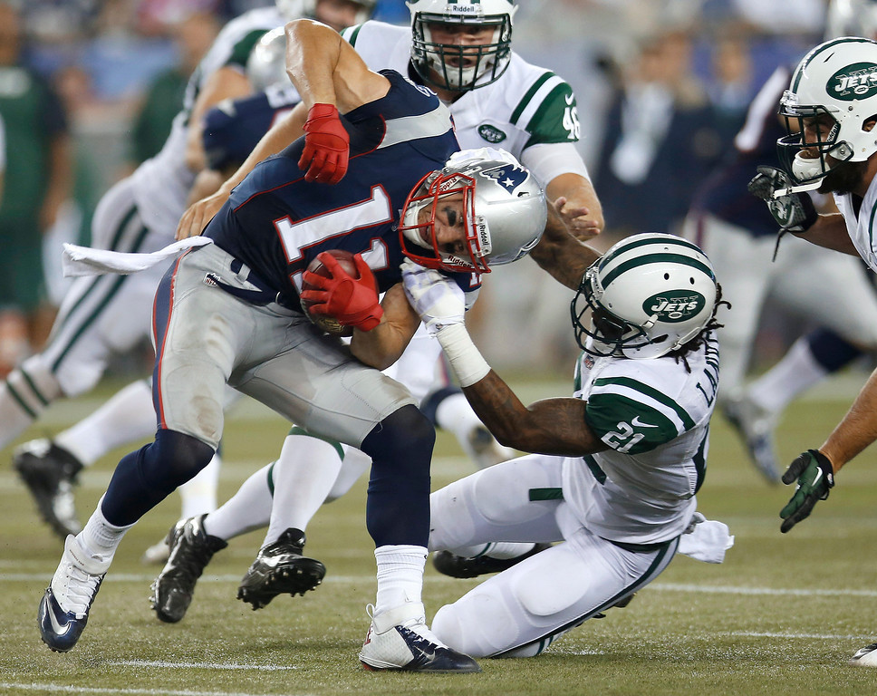 . New York Jets defensive back Ellis Lankster (21) tries to tackle New England Patriots wide receiver Julian Edelman (11) during the second quarter of an NFL football game Thursday, Sept. 12, 2013, in Foxborough, Mass. (AP Photo/Elise Amendola)