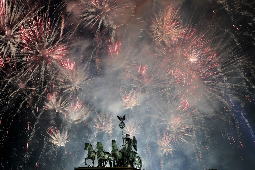 . Fireworks light the sky above the Quadriga at the Brandenburg Gate during New Year\'s celebrations shortly after midnight in Berlin, Monday, Jan. 1, 2018. (AP Photo/Markus Schreiber)