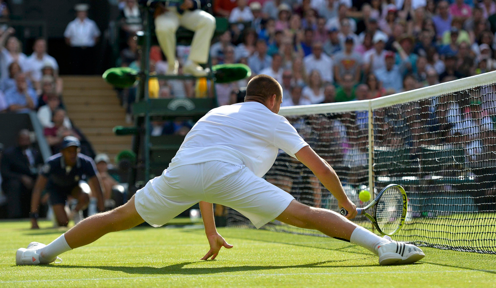 . Mikhail Youzhny of Russia hits a shot into the net during his men\'s singles tennis match against Andy Murray of Britain at the Wimbledon Tennis Championships, in London July 1, 2013.          REUTERS/Toby Melville (BRITAIN  - Tags: SPORT TENNIS)
