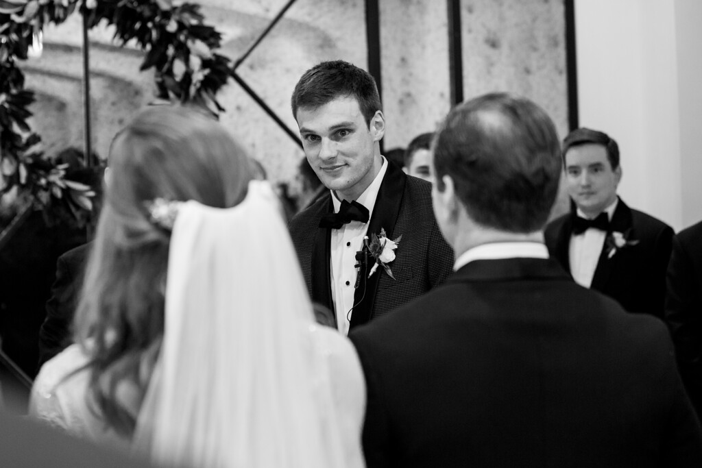 groom standing at the altar looking down the aisle towards his bride