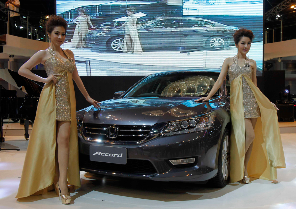 . Models pose beside a Honda Accord during a media presentation of the 34th Bangkok International Motor Show in Bangkok March 26, 2013. The Bangkok International Motor Show will be held from March 27 to April 7. REUTERS/Chaiwat Subprasom
