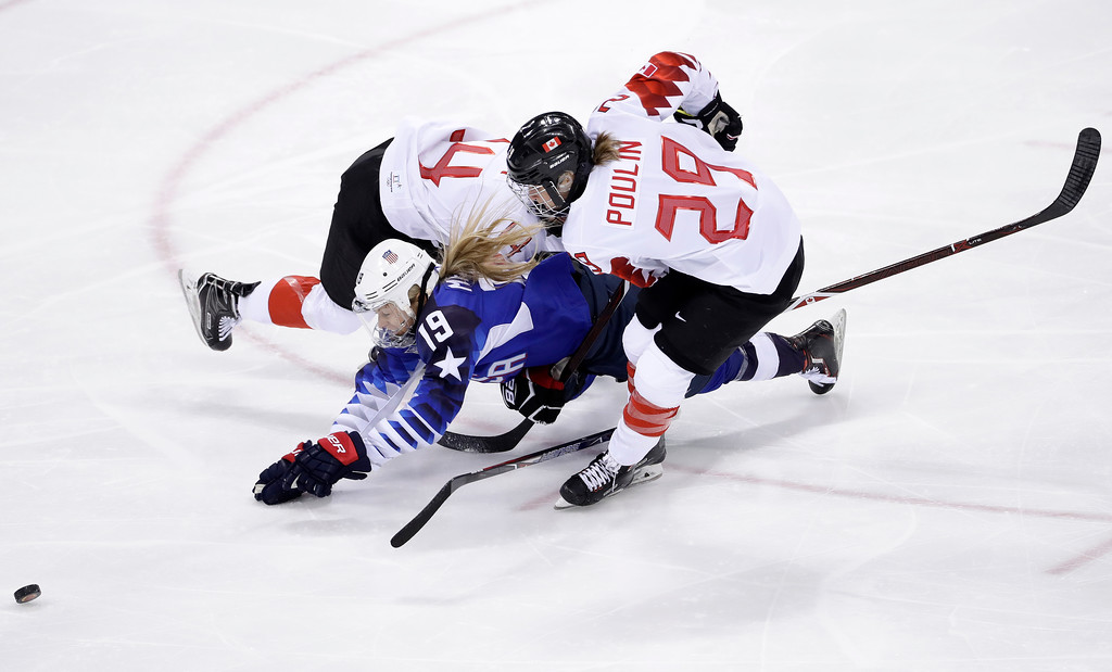 . Gigi Marvin (19), of the United States, collides between Renata Fast (14), of Canada, and Marie-Philip Poulin (29), of Canada, during the first period of the women\'s gold medal hockey game at the 2018 Winter Olympics in Gangneung, South Korea, Thursday, Feb. 22, 2018. (AP Photo/Matt Slocum)