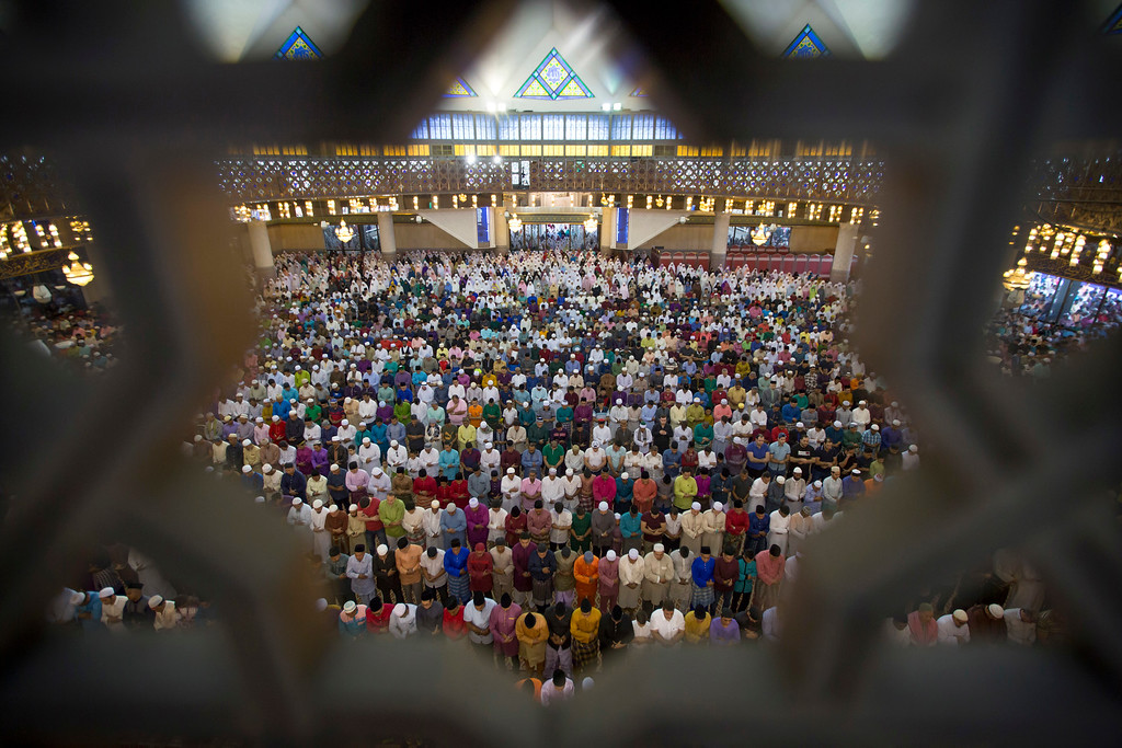 . Malaysian Muslims offer prayers during the first day of Eid al-Fitr, which marks the end of the holy fasting month of Ramadan in Kuala Lumpur, Malaysia, Friday, June 15, 2018. (AP Photo/Vincent Thian)