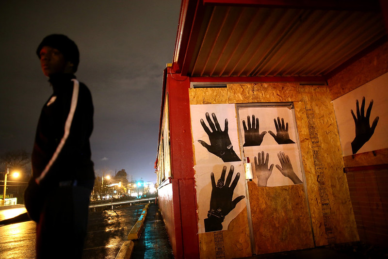 . A demonstrator stands next to a boarded up business while protesting the shooting death of 18-year-old Michael Brown on November 22, 2014 in Ferguson, Missouri. Tensions in Ferguson remain high as a grand jury is expected to decide this month if Ferguson police officer Darren Wilson should be charged in the shooting death of Michael Brown.  (Photo by Justin Sullivan/Getty Images)