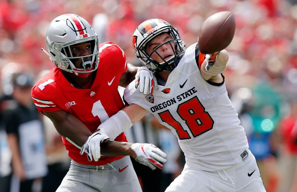 . Ohio State defensive back Jeffrey Okudah, left, knocks the ball away from Oregon State wide receiver Timmy Hernandez during the first half of an NCAA college football game Saturday, Sept. 1, 2018, in Columbus, Ohio. (AP Photo/Jay LaPrete)