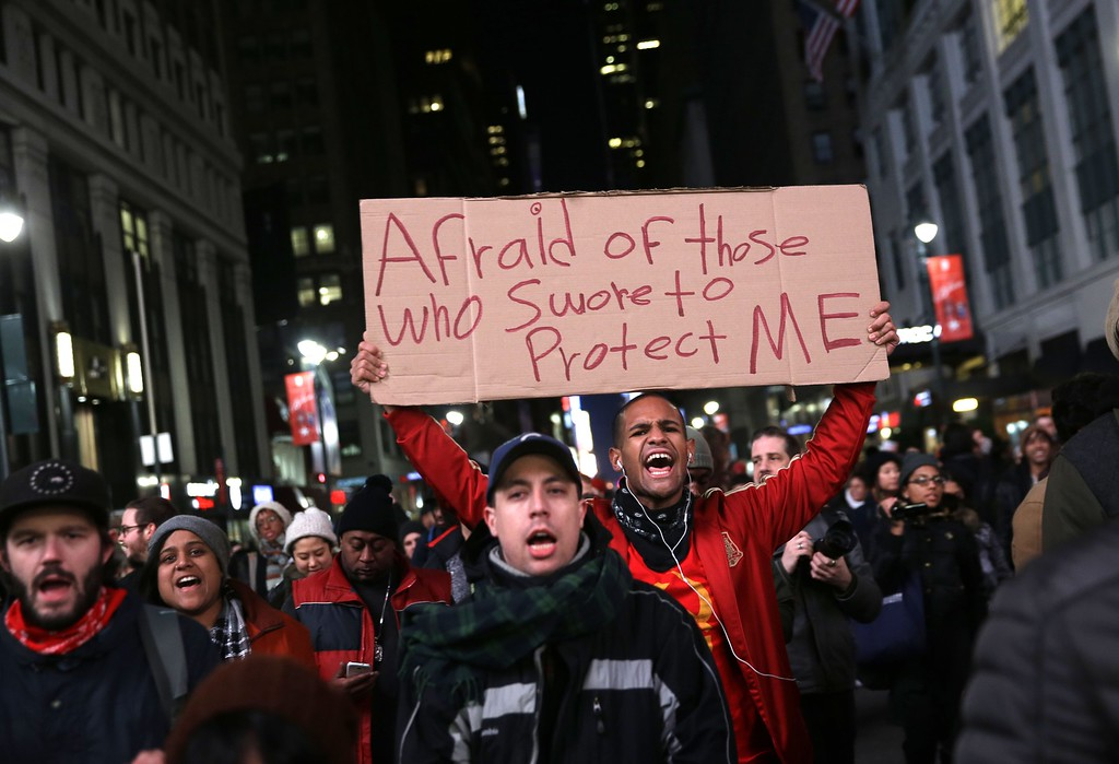 . Protesters march through the streets in response to the grand jury\'s decision in the Eric Garner case in Times Square in New York, Wednesday, Dec. 3, 2014. The grand jury cleared a white New York City police officer Wednesday in the videotaped chokehold death of Garner, an unarmed black man, who had been stopped on suspicion of selling loose, untaxed cigarettes, a lawyer for the victim\'s family said. (AP Photo/Seth Wenig)