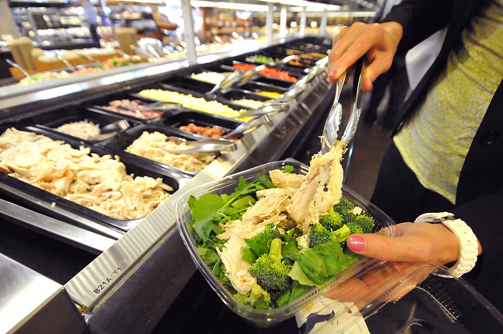 . Sue Newton of Eagan makes herself a lunch from the salad bar this month at the Lunds store at 12th Street and Hennepin Avenue in downtown Minneapolis. The store will be a model for a new Lunds location slated for downtown St. Paul. (Pioneer Press: John Doman)