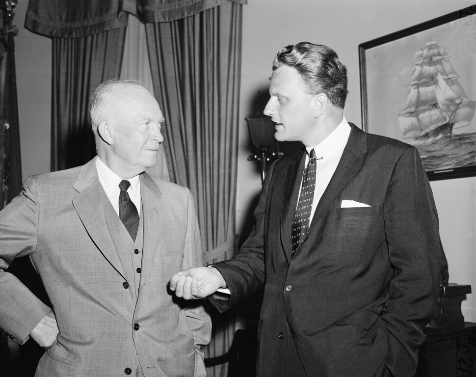 . Evangelist Billy Graham, right, talks with U.S. President Dwight Eisenhower during a visit at the White House in Washington, D.C., May 10, 1957.  (AP Photo)