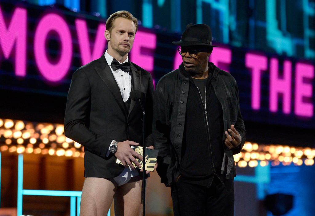 . Alexander Skarsgard, left, and Samuel L. Jackson present the award for movie of the year at the MTV Movie Awards at Warner Bros. Studio on Saturday, April 9, 2016, in Burbank, Calif. (Kevork Djansezian/Pool Photo via AP)