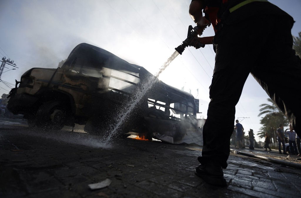 . Palestinian firefighters try to extinguish the flames in a van, that was reportedly targeted by an Israeli military strike, in Gaza City on July 31, 2014. Israel said it would not pull troops from Gaza until they finish destroying a network of cross-border tunnels, despite sharp United Nations criticism over the Palestinian civilian death toll. AFP PHOTO/ MOHAMMED ABED/AFP/Getty Images