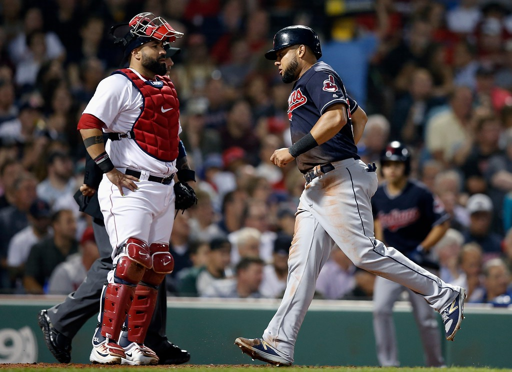. Cleveland Indians\' Melky Cabrera, right, scores in front of Boston Red Sox\'s Sandy Leon on a single by Yan Gomes during the fourth inning of a baseball game in Boston, Tuesday, Aug. 21, 2018. (AP Photo/Michael Dwyer)