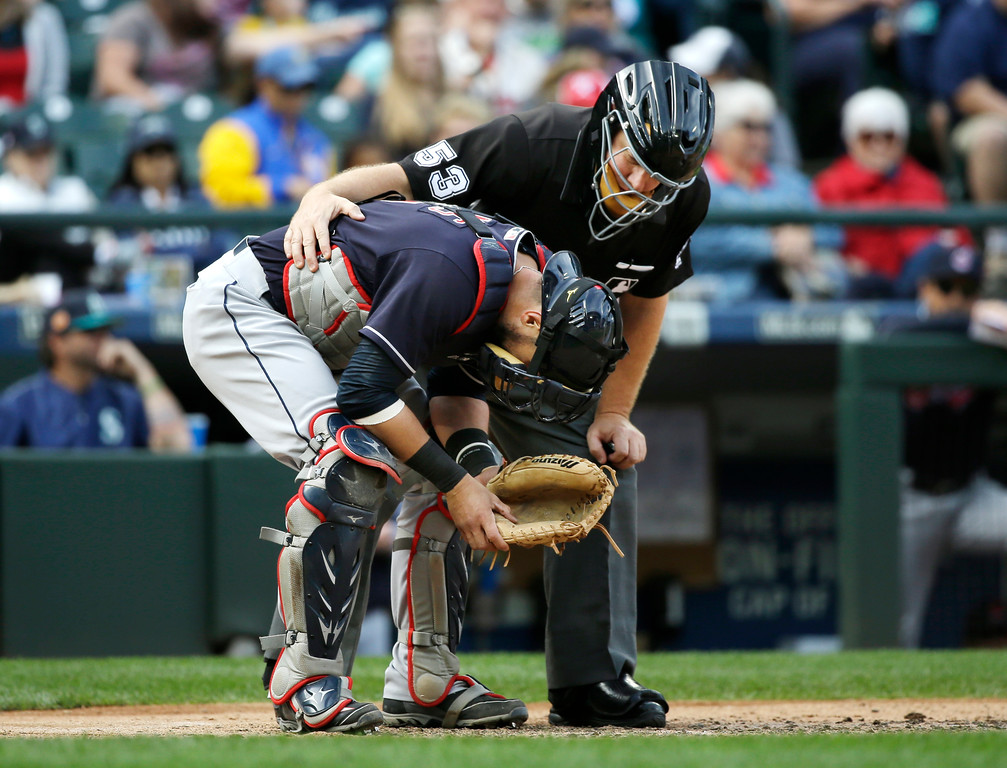 . Cleveland Indians catcher Yan Gomes is looked at by umpire Greg Gibson after Gomes was hit by a ball against the Seattle Mariners in a baseball game Saturday, Sept. 23, 2017, in Seattle. Gomes remained in the game. (AP Photo/Elaine Thompson)