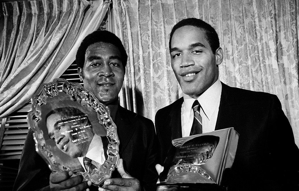 . Leroy Kelly, left, of the Cleveland Browns, and O.J. Simpson of Southern California are reflected in each other\'s trophies they received for football greatness at the annual Maxwell Football Club awards dinner in Philadelphia, Jan. 20, 1969. Kelly was presented the Bert Bell Award as outstanding pro-football player of 1968. Simpson received the award as outstanding college player of 1968. (AP Photo/Bill Ingraham)