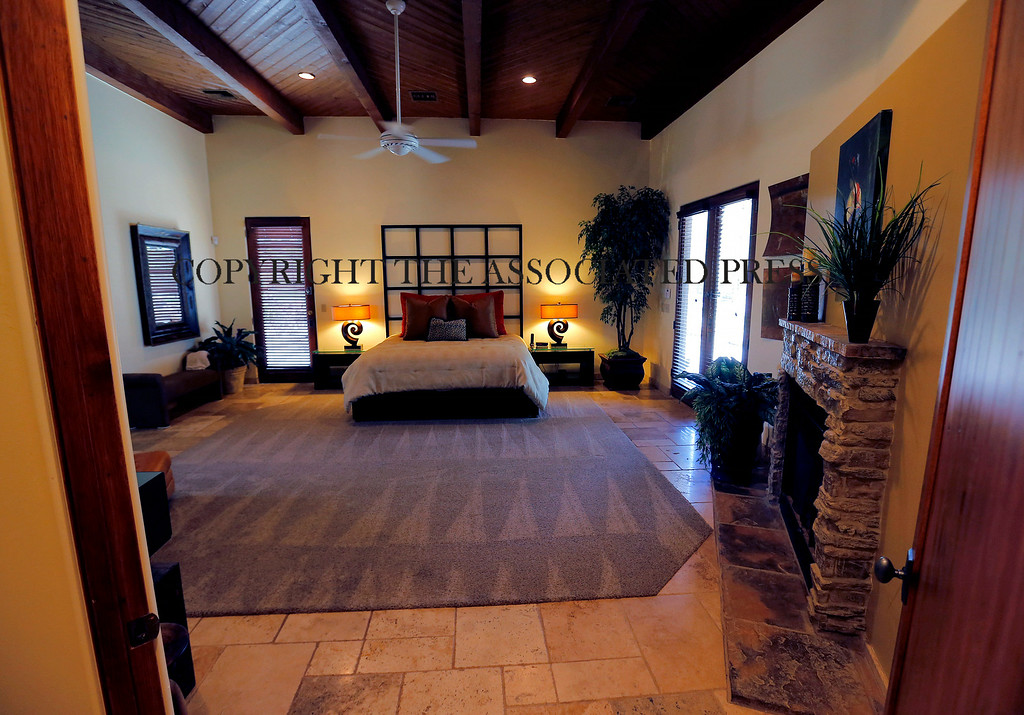 . This is a view of the master suite in a luxury home with a listing price of $1 million on Wednesday, July 30, 2014, in the Las Sendas community of Mesa, Ariz. The more than 4,000-square-foot home has a private suite with its own bath, fireplace and office, as well as a resort style back yard with a pool and hot tub. The home showcases a desert view on a golf course in the Phoenix suburb. (AP Photo/Matt York)