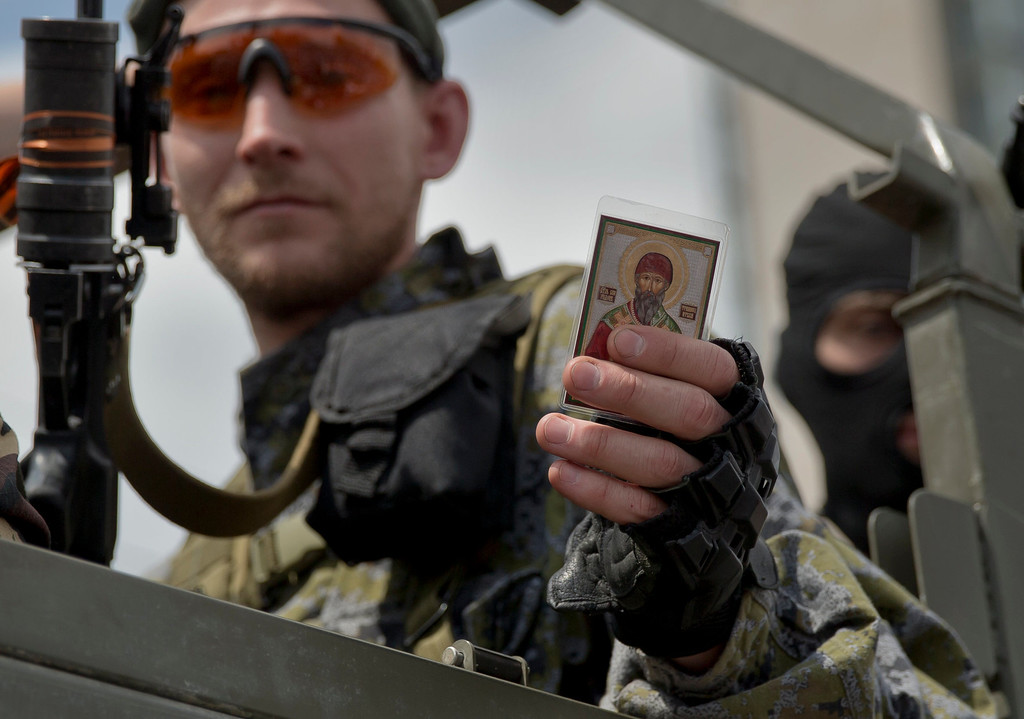 """. A Pro-Russian gunman holds an icon received from a woman in Lenin Square, Donetsk, Ukraine, Sunday, May 25, 2014. A convoy of an armored personnel carrier and seven trucks carrying several hundred heavily armed men drove through central Donetsk early Sunday afternoon and gunmen got out of the trucks, stood to attention and gave shots in the air in jubilation as a crowd of several thousand supporters cheered them and chanted: \""""Heroes!\"""". Ukraine\'s critical presidential election got underway Sunday under the wary scrutiny of a world eager for stability in a country rocked by a deadly uprising in the east. (AP Photo/Vadim Ghirda)"""