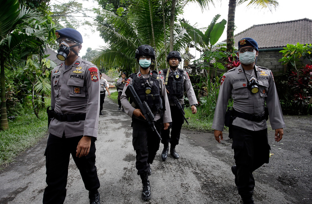 . Police officers wear masks as they patrol in a village in Karangasem, Bali, Indonesia, Tuesday, Nov. 28, 2017. Indonesia authorities raised the alert for the rumbling volcano to highest level on Monday and closed the international airport on tourist island of Bali stranding thousands of travelers. (AP Photo/Firdia Lisnawati)