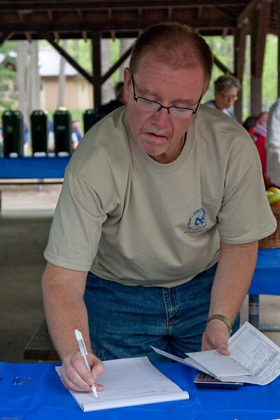 (1) Pslip Slug #: W 00020181; (2) Ridgewood, NJ; (3) 05/02/09; (4) AIDS Quilt Displayed at 11th Annual Rigewood AIDS Walk on 5/2/2009; (5) Bob Sorbanelli checks the roster of volunteers at the Eleventh Annual NJ Buddies AIDS Walk on 5/2/2009; (6) W.H. Grae for the Ridgewood News.