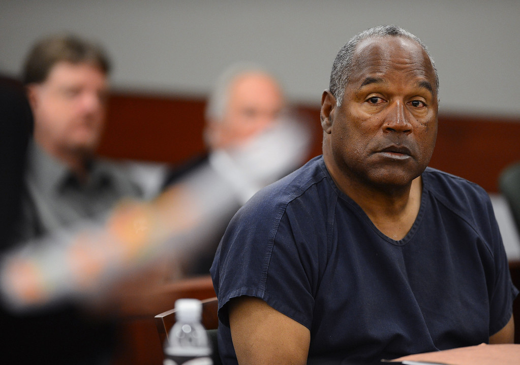 . O.J. Simpson appears on the second day of an evidentiary hearing for  Simpson in Clark County District Court, Tuesday, May 14, 2013 in Las Vegas.  The hearing is aimed at proving Simpson\'s trial lawyer, Yale Galanter,  had conflicted interests and shouldn\'t have handled Simpson\'s case. Simpson is serving nine to 33 years in prison for his 2008 conviction in the armed robbery of two sports memorabilia dealers in a Las Vegas hotel room.  Judge Bell let Simpson have one hand unshackled to drink water and take notes.  His left hand was still cuffed to the arm of his chair during the hearing. (AP Photo/Ethan Miller, Pool)