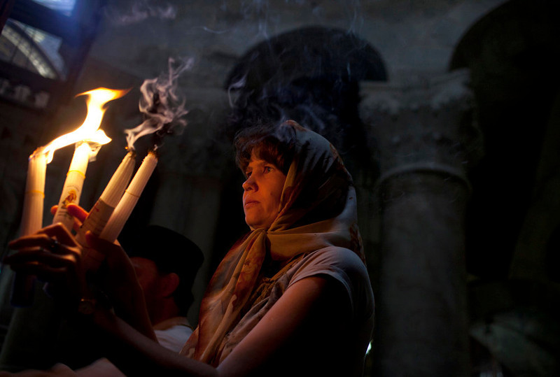 . A Christian worshipper lights candles prior to the Orthodox Easter service at the Church of the Holy Sepulchre, traditionally believed to be the burial site of Jesus Christ, in Jerusalem\'s Old City, Sunday, May 5, 2013. (AP Photo/Sebastian Scheiner)