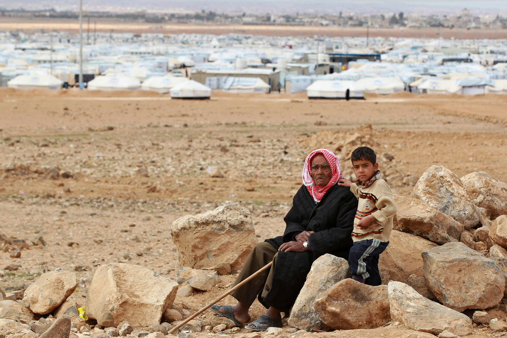 Description of . A Syrian refugee is seen with his grandson at Al- Zaatri refugee camp, in the Jordanian city of Mafraq, near the border with Syria February 12, 2013. REUTERS/Muhammad Hamed