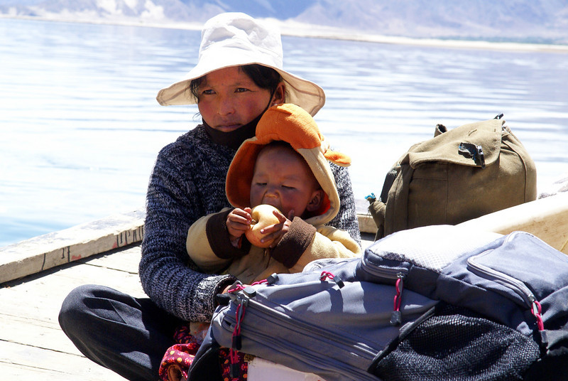 Small Tibetan boy enjoying apple with mother on ferry.