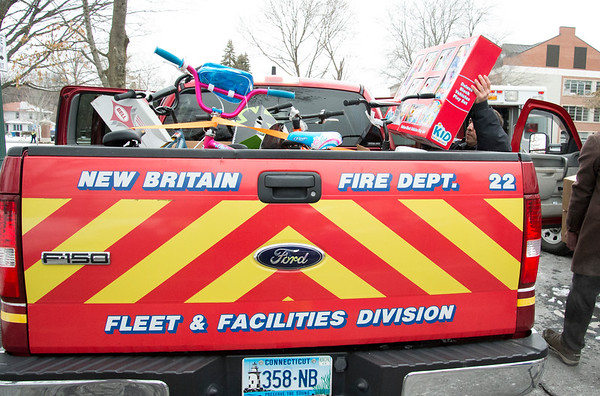 12/13/19 Wesley Bunnell | StaffrrToys, warm clothes, non perishable food items were collected on Friday from 6 a.m. until noon outside of CCSU's Davidson Hall in conjunction with CCSU and The Anna Grace Project's Love Wins. NBFD's Anthony Tirado loads toys onto a fire department truck.