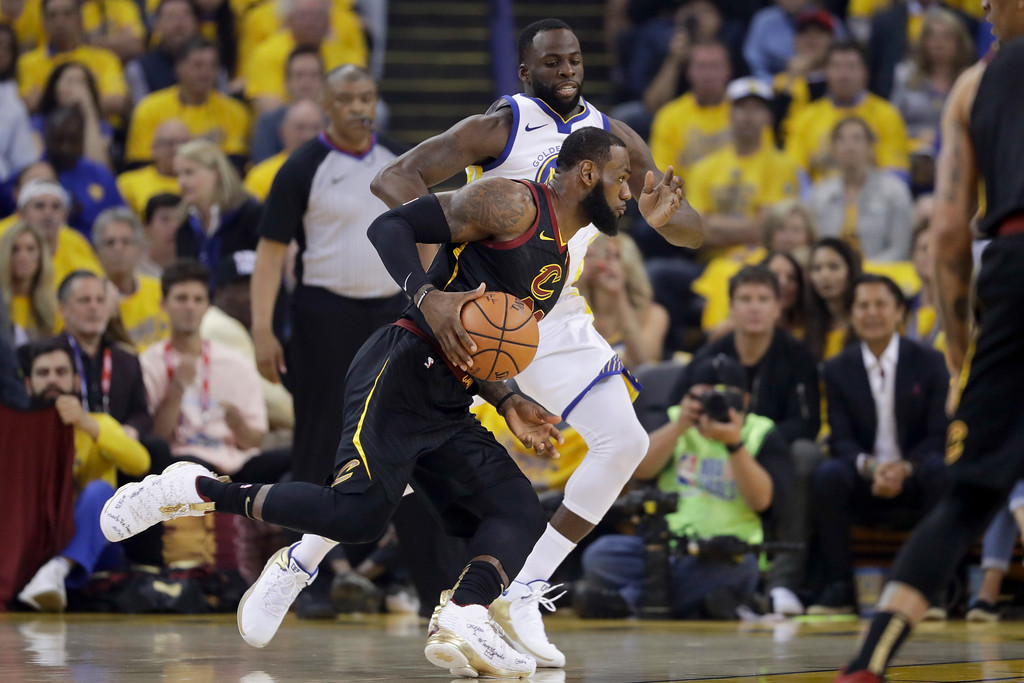 . Cleveland Cavaliers forward LeBron James, foreground, drives against Golden State Warriors forward Draymond Green during the first half of Game 1 of basketball\'s NBA Finals in Oakland, Calif., Thursday, May 31, 2018. (AP Photo/Marcio Jose Sanchez)