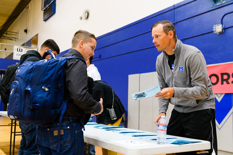 PE/weights teacher TJ Tomlin gives schedules to junior students. Back to school day at McNary High School on Wednesday, September 4, 2019 in Keizer, Ore.