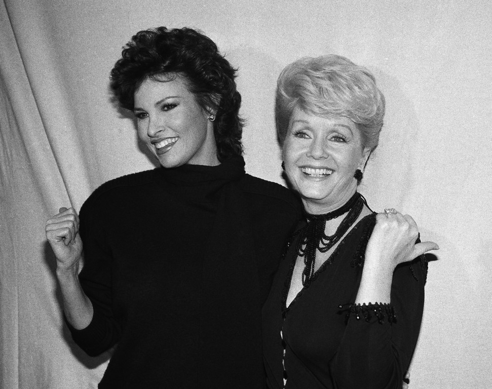 ". Debbie Reynolds, right, poses backstage with Raquel Welch after Welch\'s performance in ""Woman of the Year\"" Thursday, Dec. 31, 1982 in New York. Reynolds replaced Welch who took a maternity leave from the play. (AP Photo/Perez)"