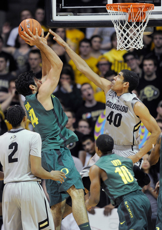 . BOULDER, CO. - MARCH 7: Colorado center Josh Scott (40) went for a block on an attempt from Oregon forward Arsalan Kaemi (14) in the second half. The University of Colorado men\'s basketball team defeated Oregon 76-53 Thursday night, March 7, 2013 at the CU Events Center in Boulder. (Photo By Karl Gehring/The Denver Post)