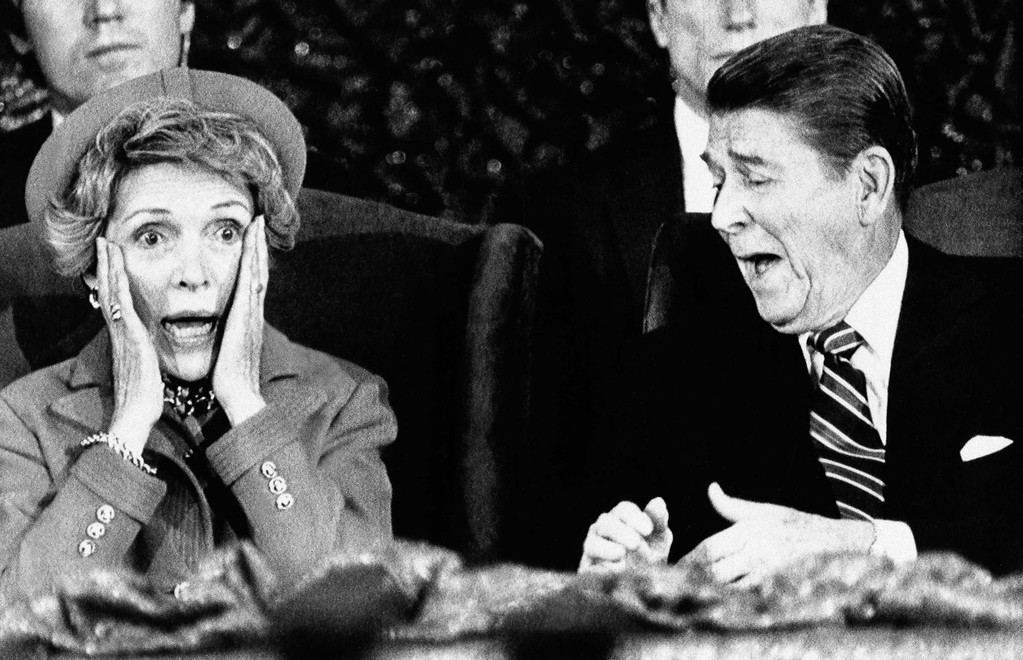 . President  Ronald Reagan and wife Nancy  react after Mrs. Reagan sat down after speaking and forgot to introduce the President at the Capital Center in Landover, Md., Monday, Jan. 21, 1985, during an event held for those who would have participated in the inaugural parade, which was canceled because of bad weather. (AP Photo/Scott Stewart)