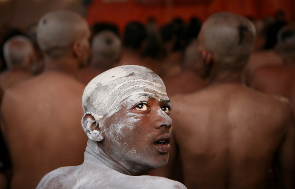""". A Naga Sadhu, center, watches as other Hindu holy men of the Juna Akhara sect participate in a rituals that are believed to rid them of all ties in this life and dedicate themselves to serving God as a \""""Naga\"""" or naked holy men, at Sangam, the confluence of the Ganges and Yamuna River during the Maha Kumbh festival in Allahabad, India, Wednesday, Feb. 6, 2013. The significance of nakedness is that they will not have any worldly ties to material belongings, even something as simple as clothes. This ritual that transforms selected holy men to Naga can only be done at the Kumbh festival. (AP Photo/ Rajesh Kumar Singh)"""