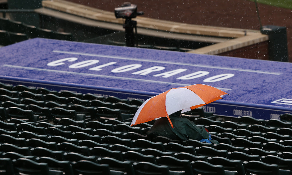 . A lone fan sits under an umbrella as a wintry mix of rain and snow falls on Coors Field before the Colorado Rockies host the Arizona Diamondbacks in a baseball game in Denver on Sunday, April 6, 2014. (AP Photo/David Zalubowski)