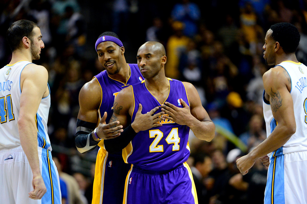 . Los Angeles Lakers shooting guard Kobe Bryant (24) wipes his hands on his jersey as center Dwight Howard (12) leans over his shoulder against before the first half against the Denver Nuggets at the Pepsi Center on Wednesday, December 26, 2012. AAron Ontiveroz, The Denver Post