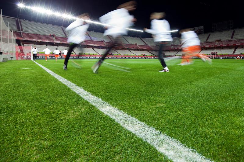 Football players training by night. Sanchez Pizjuan stadium, Seville, Spain.