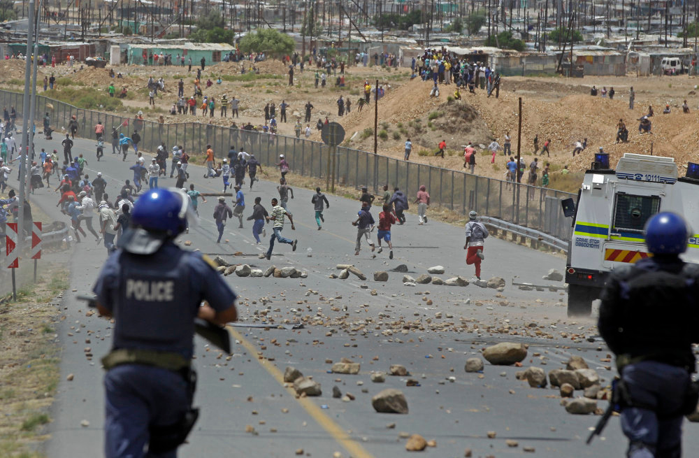 Description of . Striking farm workers run away from South African police after they fired rubber bullets at  demonstrators in De Doorns , South Africa, Thursday, Jan 10, 2013. Striking farm workers in South Africa have clashed with police for a second day during protests for higher wages. The South African Press Association says police on Thursday fired rubber bullets at rock-throwing demonstrators in the town of De Doorns in Western Cape province, and protests were occurring in at least two other towns. (AP Photo/Schalk van Zuydam)