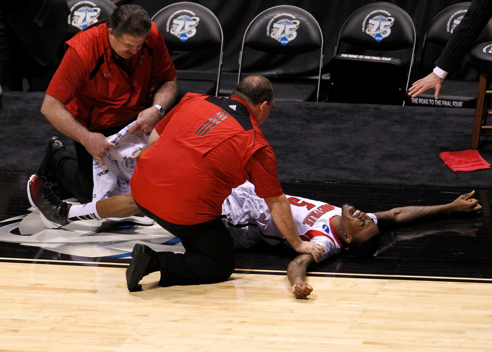 Description of . Louisville Cardinals guard Kevin Ware (5) is attended to by medical staff after breaking his leg in the first half against the Duke Blue Devils during their Midwest Regional NCAA men's basketball game in Indianapolis, Indiana, March 31, 2013.   REUTERS/John Sommers II