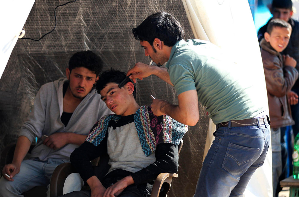 . A Syrian refugee gets his hair cut at the Bab Al-Salam refugee camp in Azaz, near the Syrian-Turkish border March 25, 2013. REUTERS/Giath Taha