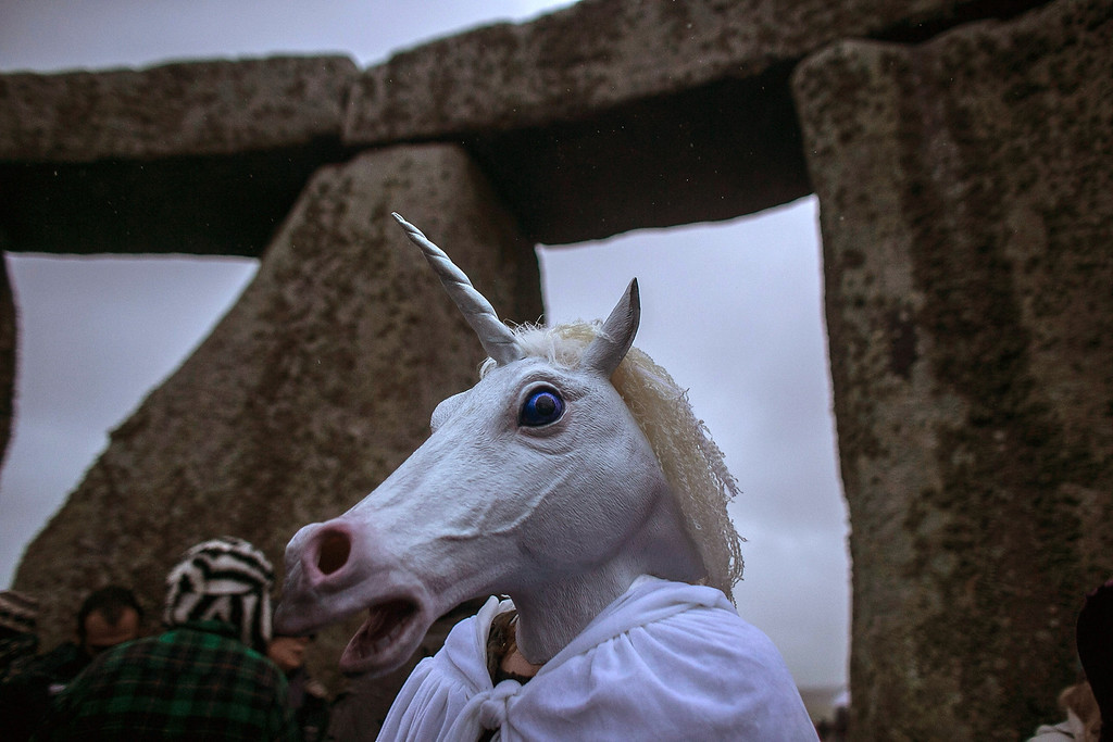 . A woman wearing a unicorn mask watches as druids, pagans and revelers gather, hoping to see the sun rise as they take part in a winter solstice ceremony at Stonehenge on December 21, 2013 in Wiltshire, England.  (Photo by Matt Cardy/Getty Images)
