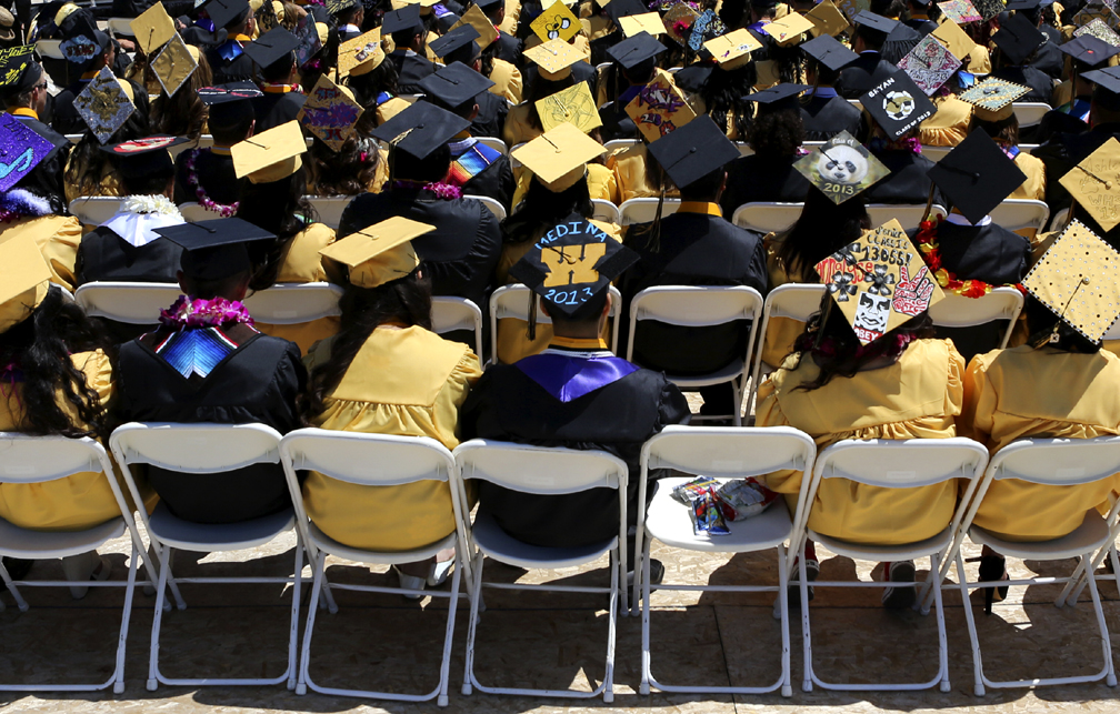 . Dozens of black and yellow graduation caps flood the Watsonville High football field on Friday afternoon during the 2013 graduation ceremony. (Kevin Johnson/Sentinel)