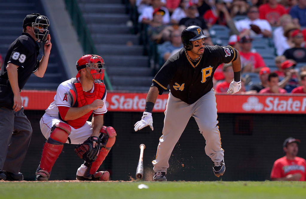 . Pittsburgh Pirates\' Pedro Alvarez, right, hits a double as Los Angeles Angels catcher Chris Iannetta, center, looks on during the 10th inning of a baseball game on Sunday, June 23, 2013, in Anaheim, Calif. (AP Photo/Mark J. Terrill)