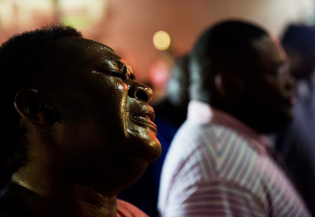 . Lisa Doctor joins a prayer circle early Thursday, June 18, 2015,  down the street from the Emanuel AME Church following a shooting Wednesday night in Charleston, S.C. (AP Photo/David Goldman)