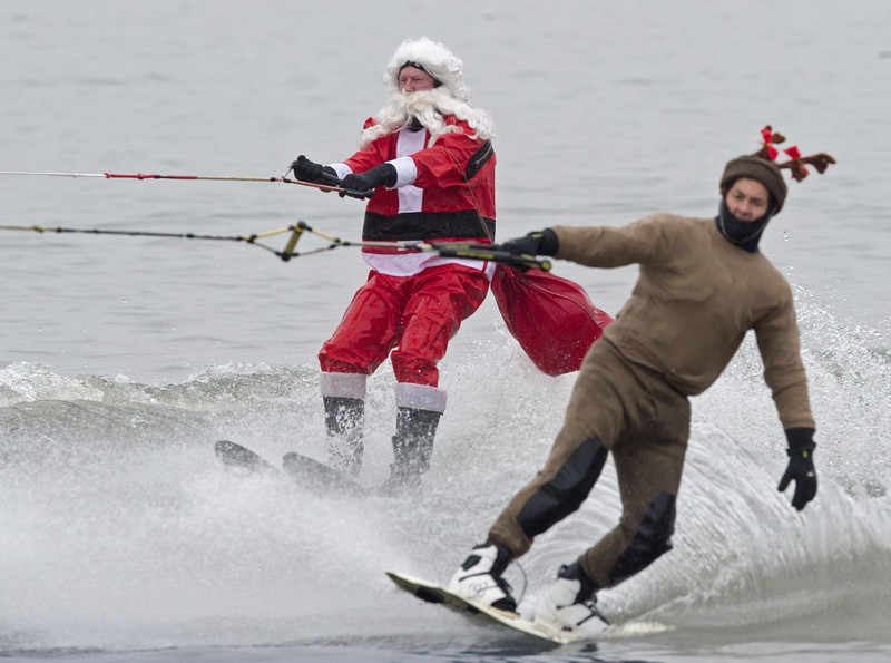 . A water-skiing Santa and Elf are towed behind a boat and riding up the Potomac River off Old Town Alexandria, Virginia, not far from washington, DC December 24, 2014.   PAUL J. RICHARDS/AFP/Getty Images