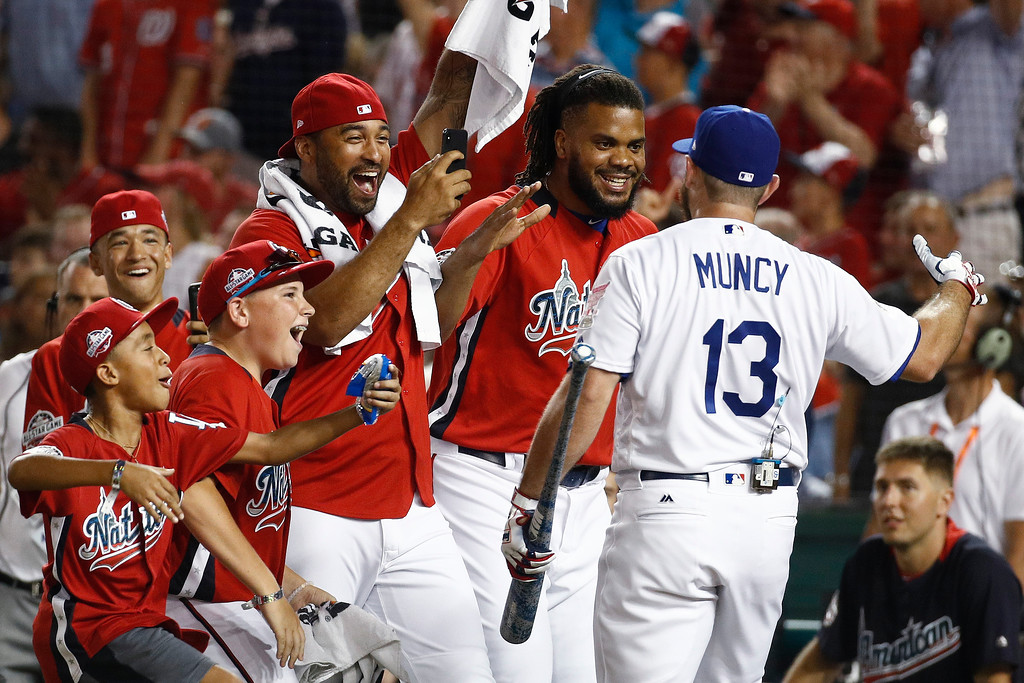 . Los Angeles Dodgers Max Muncy (13) is congratulated by his National League teammates during the MLB Home Run Derby, at Nationals Park, Monday, July 16, 2018 in Washington. The 89th MLB baseball All-Star Game will be played Tuesday. (AP Photo/Patrick Semansky)