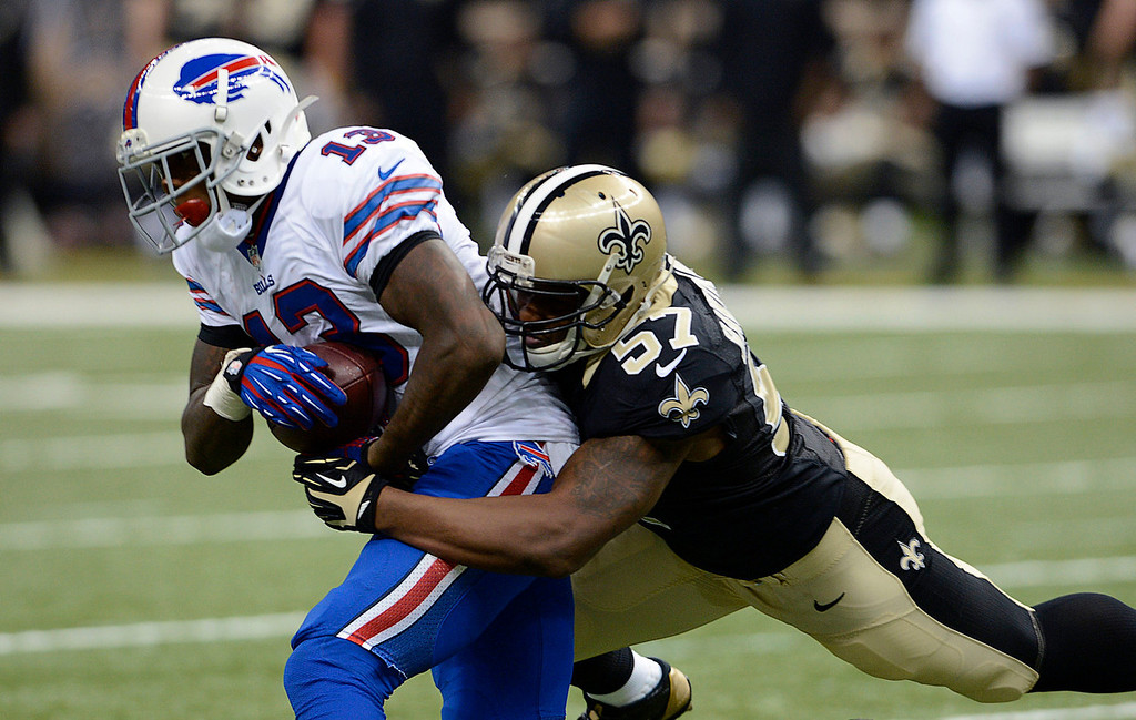 . Buffalo Bills wide receiver Steve Johnson (13) carries as he is tackled by New Orleans Saints outside linebacker David Hawthorne (57) during the second half of an NFL football game in New Orleans, Sunday, Oct. 27, 2013. (AP Photo/Bill Feig)