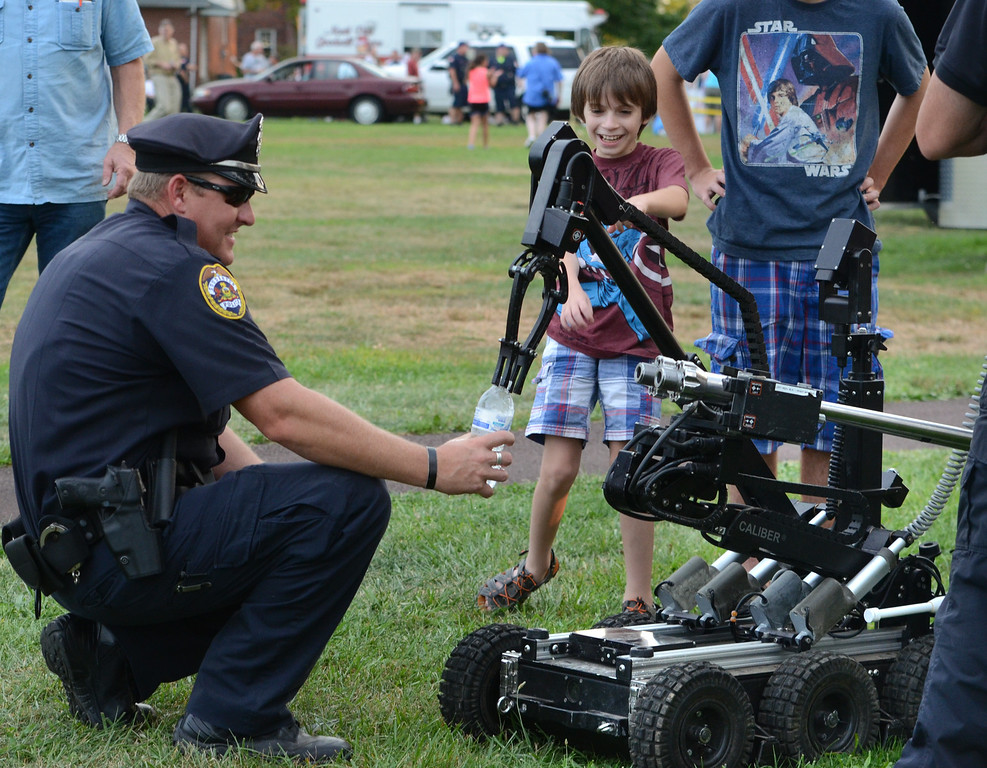. Souderton Police officer Jeff Lukens holds a bottle as the Montgomery County Sheriff\'s Department Bomb Squad gives a demonstration with one of their robots during the Souderton and Telford Police Departments Community Night Out on Tuesday evening August 19,2014. Photo by Mark C Psoras/The Reporter