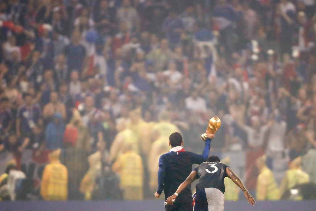 . French players celebrate with the trophy under the rain after the final match between France and Croatia at the 2018 soccer World Cup in the Luzhniki Stadium in Moscow, Russia, Sunday, July 15, 2018. (AP Photo/Natacha Pisarenko)