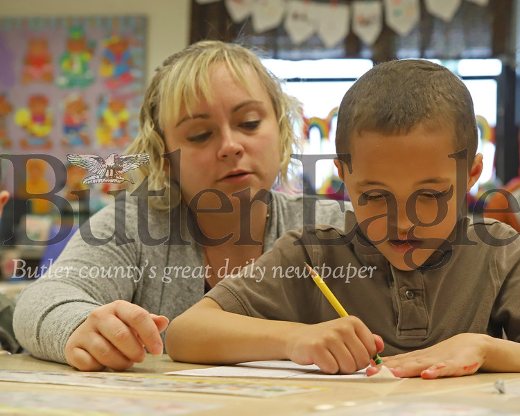 McQuistion Elementary teacher Rene Ruffner helps first grader Kayden Ellis with his Mother's Day note.Seb Foltz/Butler Eagle