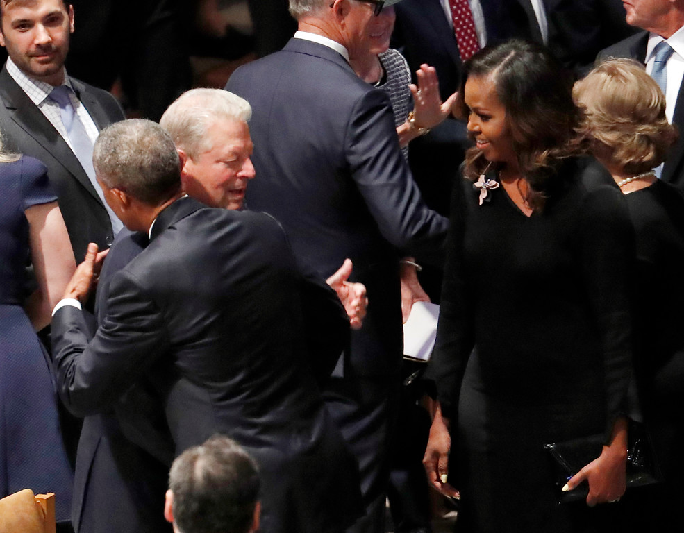 . Former President Barack Obama hugs former vice president Al Gore as former first lady Michelle Obama watches before the memorial services for Sen. John McCain, R-Ariz., at Washington National Cathedral in Washington, Saturday, Sept. 1, 2018. McCain died Aug. 25, from brain cancer at age 81. (AP Photo/Pablo Martinez Monsivais)