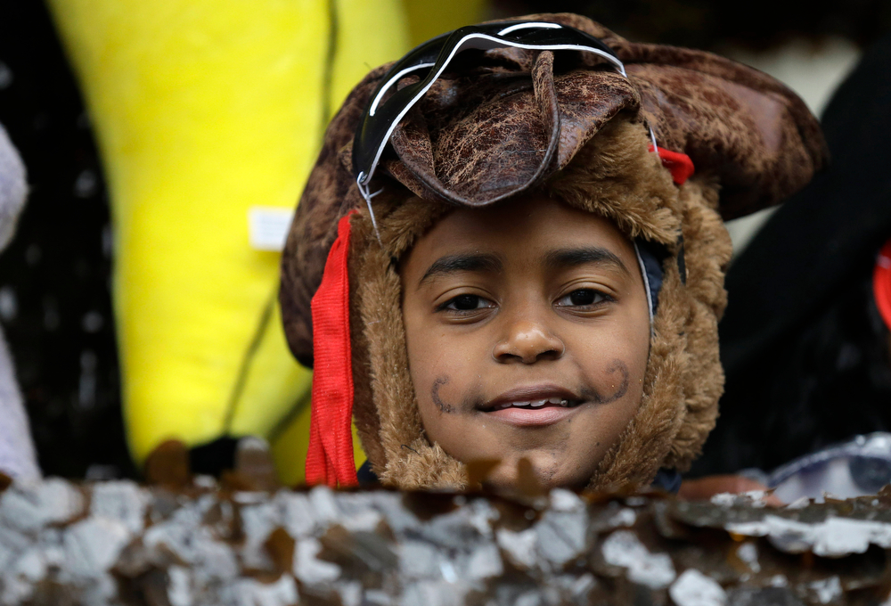 Description of . A child in costume peers from a float in the Krewe of Elks during Mardi Gras in New Orleans, Tuesday, March 4, 2014. Rain and unusually cold temperatures kept most of the normally massive and festive crowds away.  (AP Photo/Gerald Herbert)
